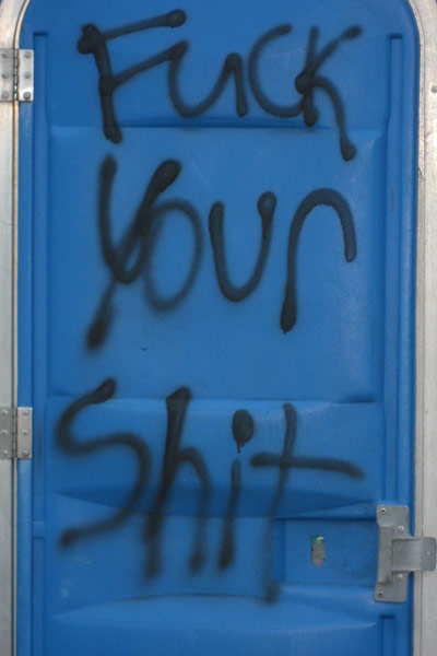 "Obscene.. yet entertaining. ""Fuck your shit"" tagged on a porta potty."